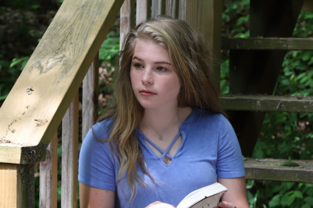Teen reading Bible on stairs.